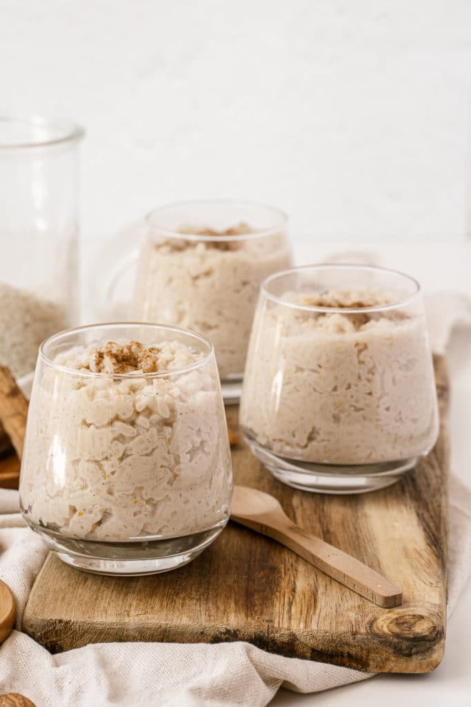 Glasses of stovetop rice pudding served on top of a wooden board and topped with extra cinnamon and almonds