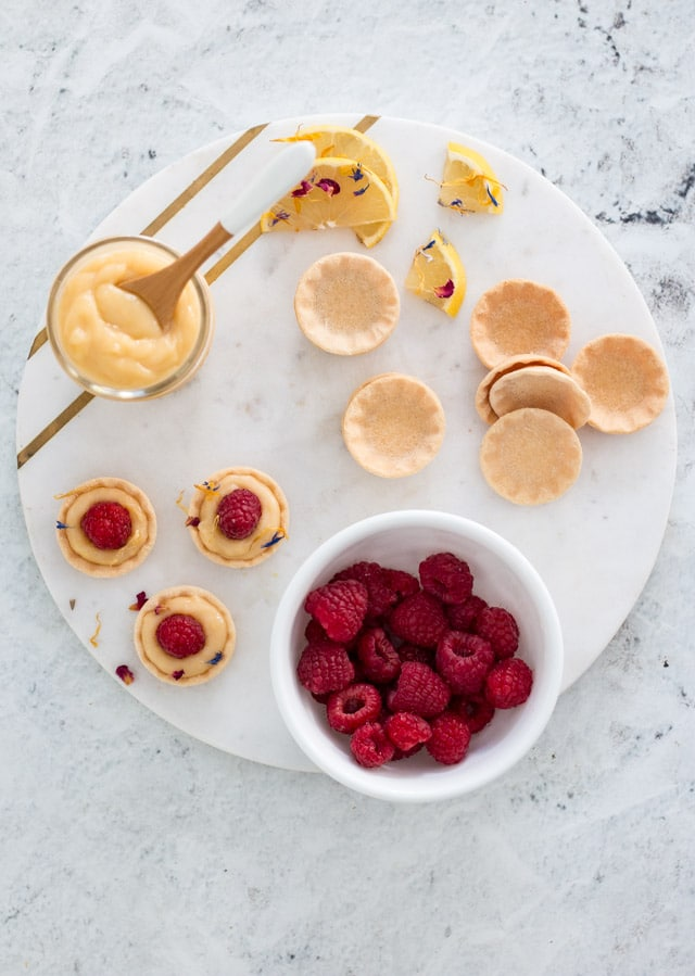 overhead shot of mini lemon tarts being assembled with all of the ingredients spread on a white and gold serving platter