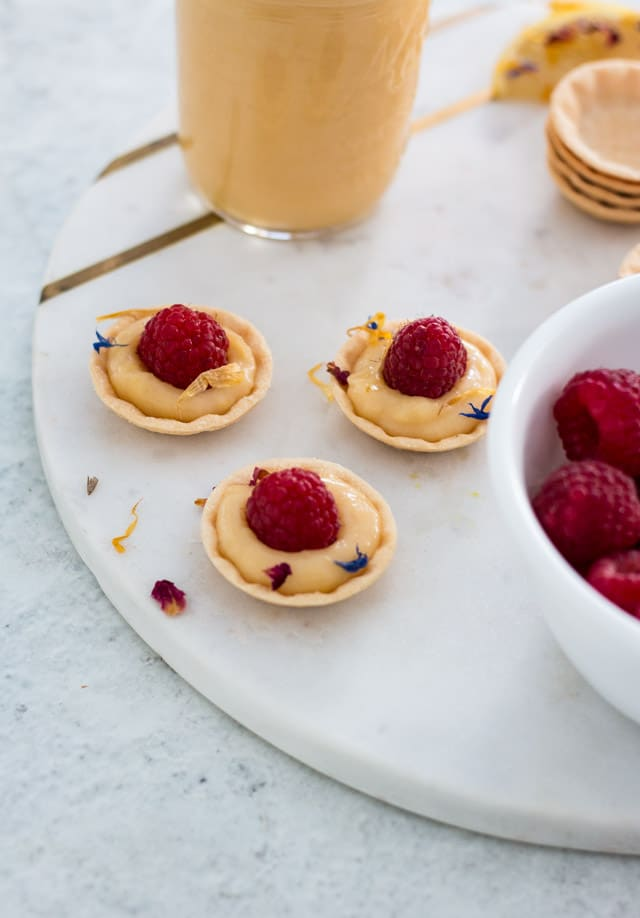 Up close shot of 3 prepared mini lemon tarts on a white and gold serving tray with a glass jar of curd and fresh raspberries in the background