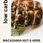 Macadamia Nut Chicken Breasts sliced and served with fresh herbs on a white platter plate