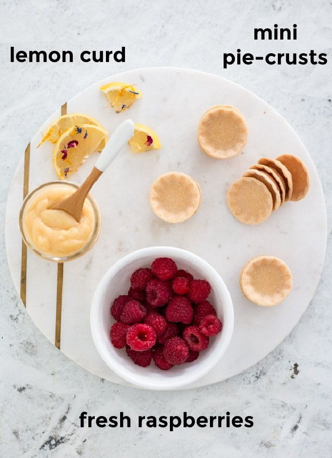 overhead labeled shot of ingredients needed to make lemon curd tarts: canape bases, lemon curd and fresh raspberries