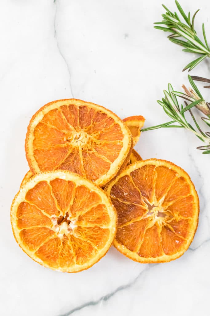 Dried orange slices stacked together against a white background, with some rosemary sprigs in the background.
