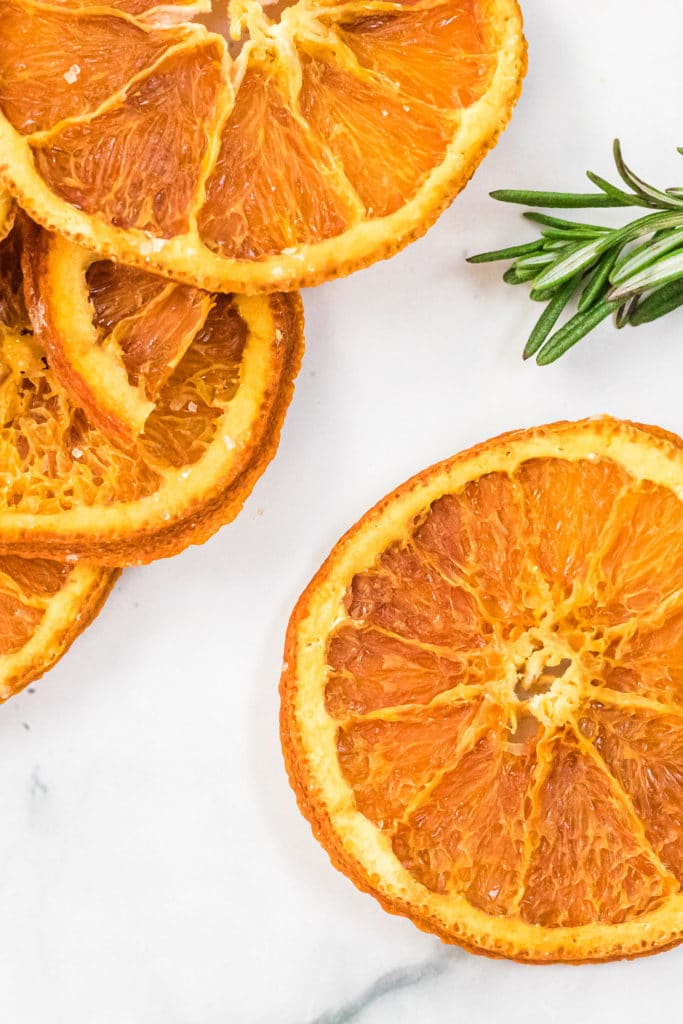 overhead shot of dehydrated orange slices with a sprig of fresh rosemary against a white background