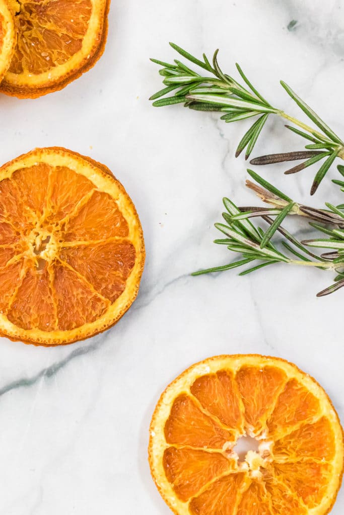 Drehydrated orange slices spread out across a white background with sprigs of fresh rosemary in the background