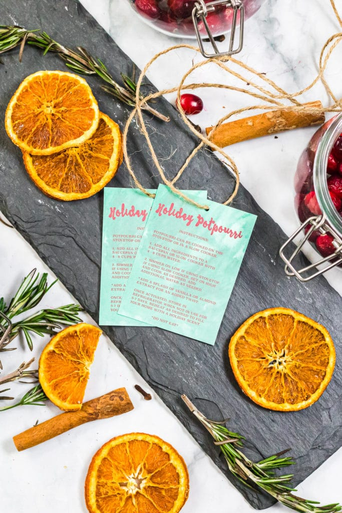 Overhead shot of gift tags with dehydrated orange slices surrounding it