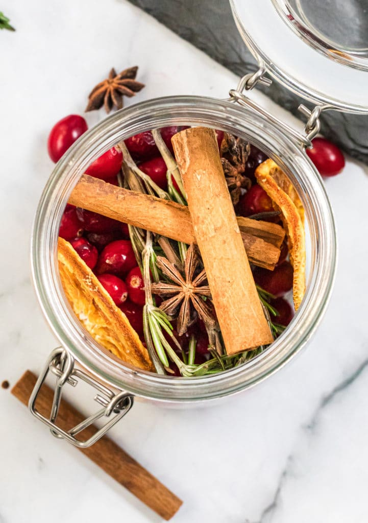 Overhead shot of a glass jar containing homemade potpourri and dried orange slices