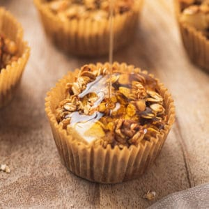 Maple syrup being drizzled on apple cinnamon oatmeal cups