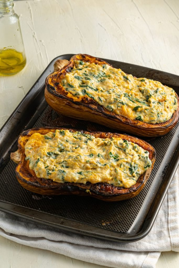 Roasted and stuffed butternut squash on a baking tray to be baked until the cheese has melted