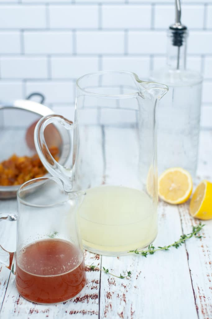 Peach honey simple syrup in a small jug being added to a lemon juice, soda, and gin mixture in a large jug