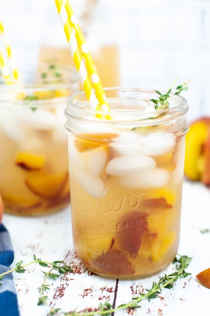 Front shot of a peach gin cocktail being served in a mason jar loaded with ice and a sprig of fresh thyme, which a yellow straw