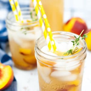 overhead shot of a fresh peach and honey cocktail served in a glass mason jar with some yellow polkadot straws