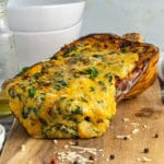 Front up close shot of melted four cheese mixture coming out of a roast stuffed butternut squash on a wooden board