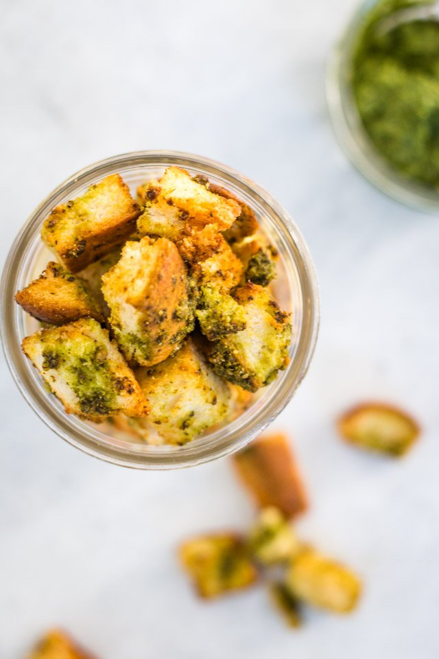 Up close overhead shot of crunchy homemade croutons stored in a glass jar