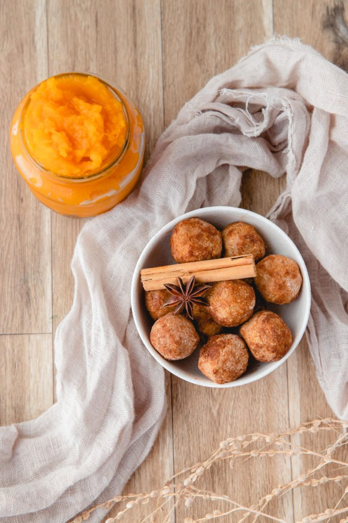 No Bake Pumpkin Balls piled in a white bowl and topped with cinnamon sticks and star anise with a jar of pumpkin puree in the background