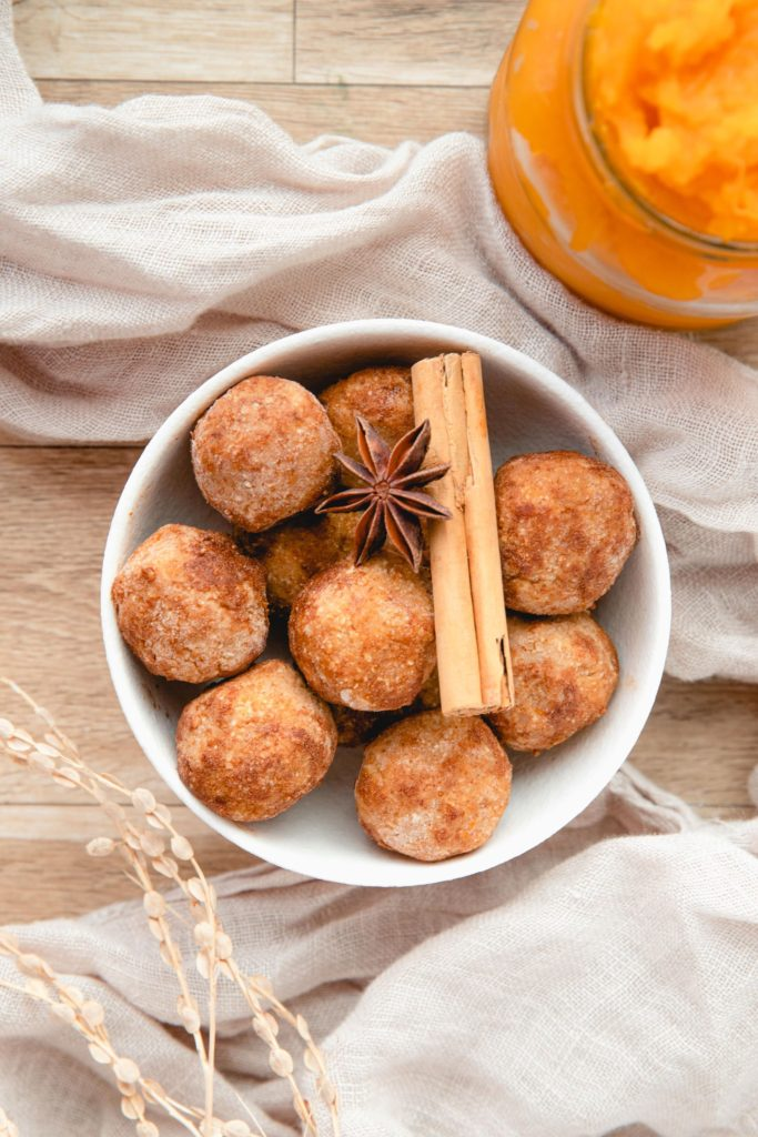 Pumpkin Protein Balls piled in a white bowl and topped with cinnamon sticks and star anise with a jar of pumpkin puree in the background