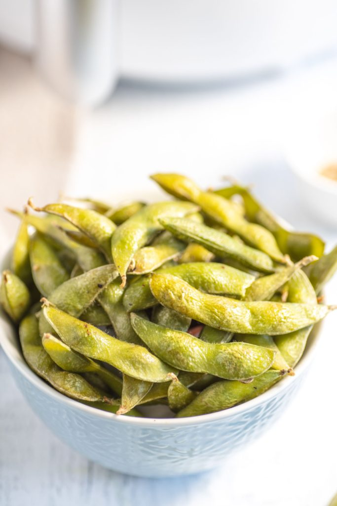 Up close shot of a bowl of cooked edamame beans in a small off-white bowl