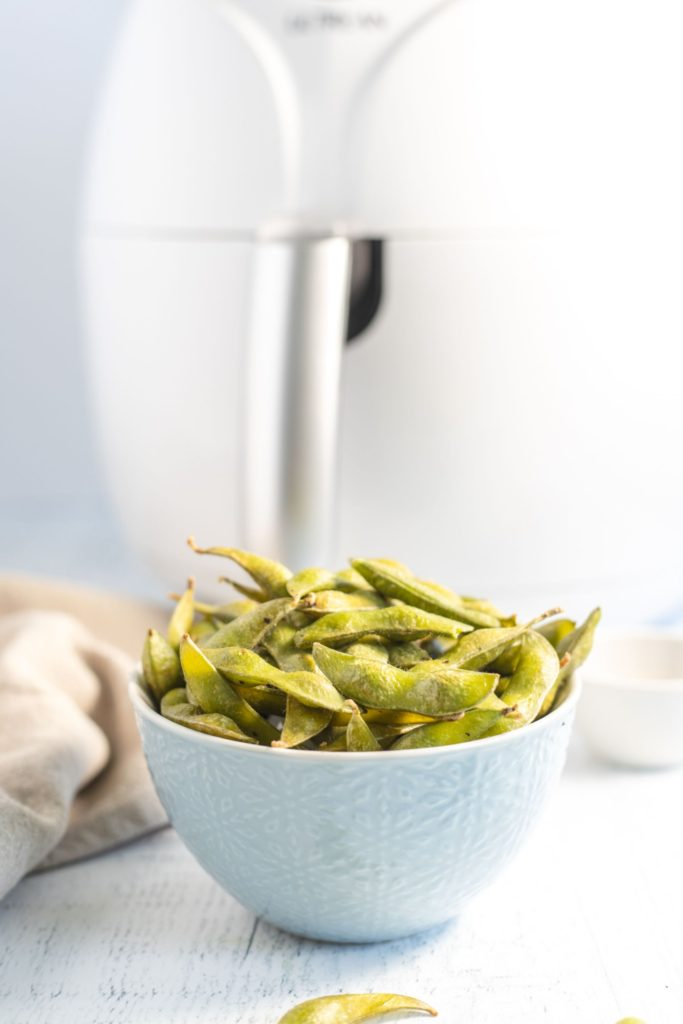 Cooked sesame edamame served in a small off-white bowl in front of an air fryer