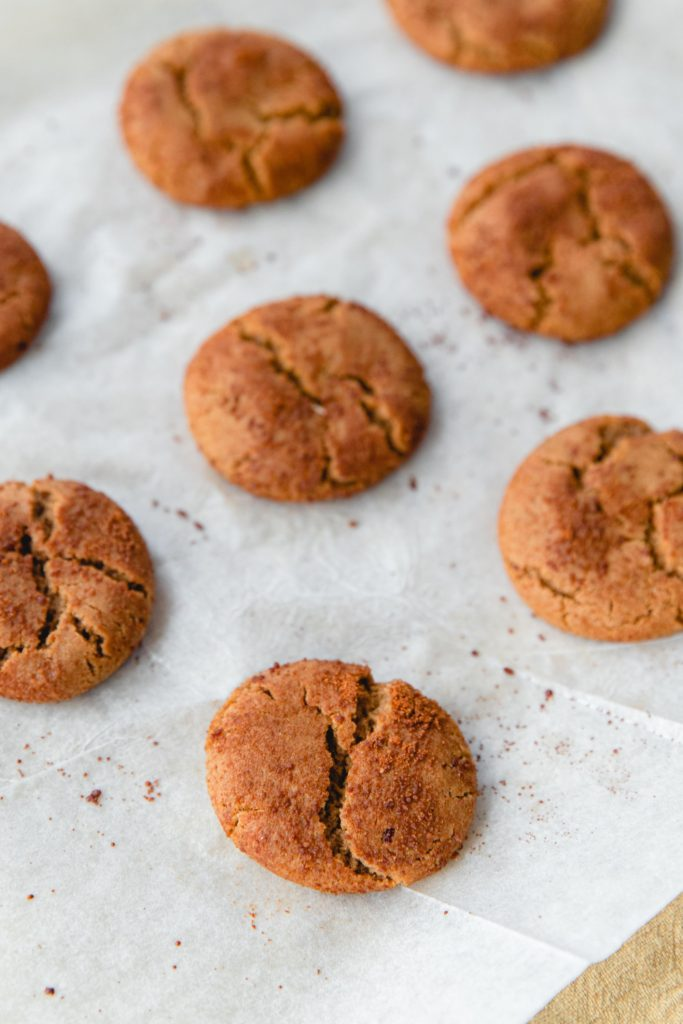 Crinkly fresh baked gingersnap cookies on a piece of parchment paper