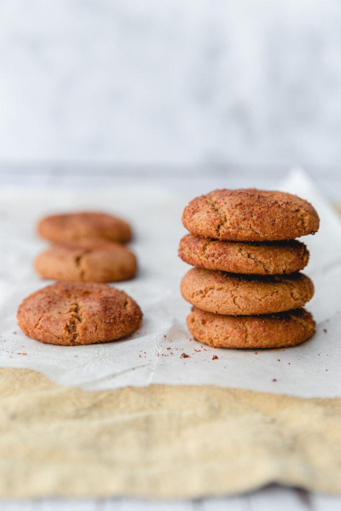 A stack of gingersnap cookies on a piece of baking paper