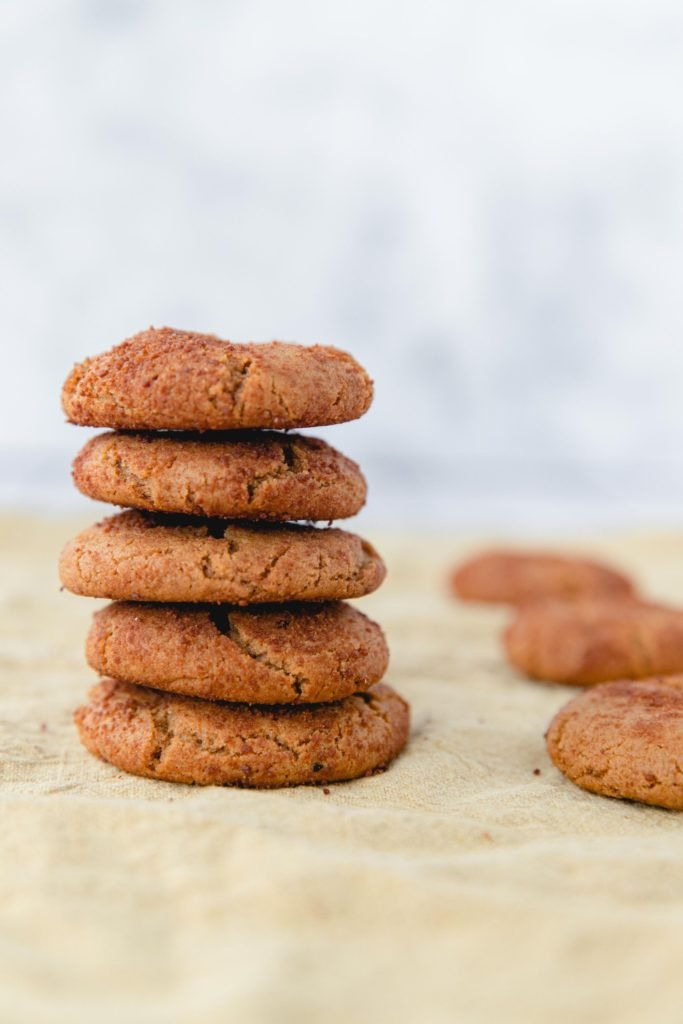 Gingersnap cookies without molasses stacked high on some parchment paper with a few spare cookies scattered in the background