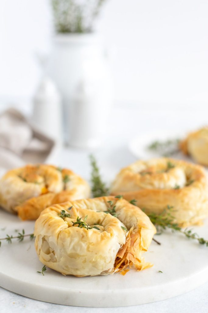 Pumpkin hand pies served on a white plate with fresh thyme sprinkled around