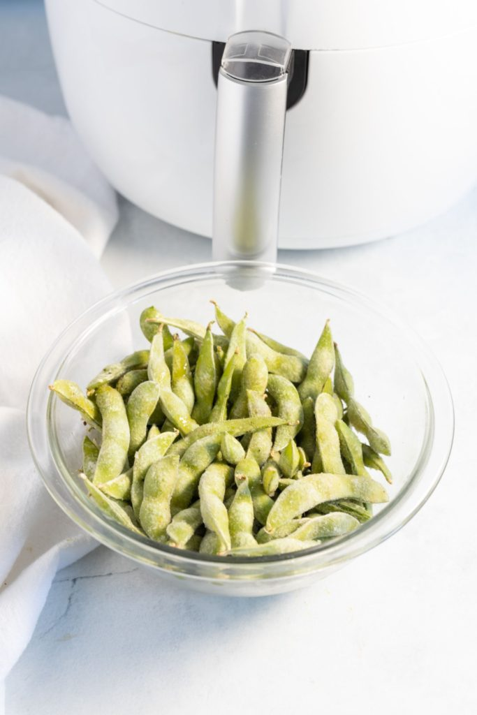 Frozen edamame in a small glass bowl in front of a white air fryer