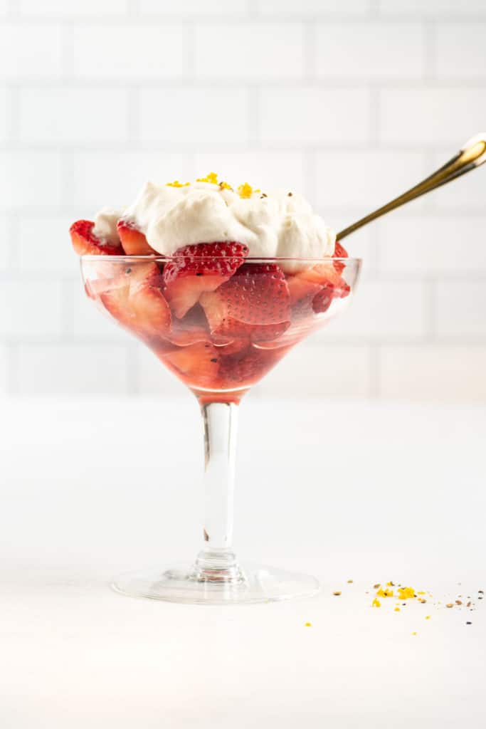 Front shot of macerated strawberries topped with whipped cream and served in a fancy glass