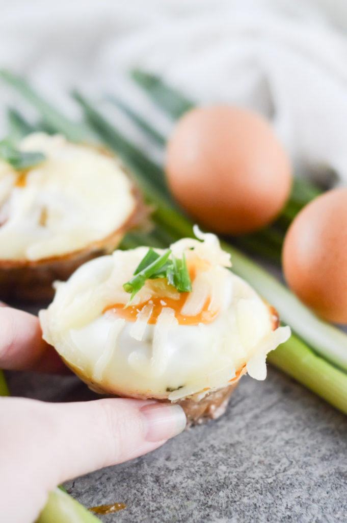 Hand grabbing Pork Sausage and Egg Muffin Cups
