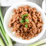 korean style spicy pork mince served in a white bowl with spring onions in the background
