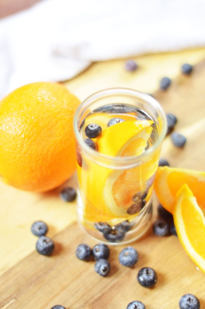 Blueberries and orange wedges served in a small glass with extra blueberries and oranges scattered around